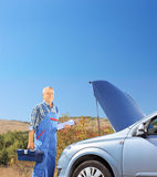 Mechanic standing near a broken car with open hood, on a road Royalty Free Stock Photos