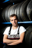 Mechanic standing next to tire shelves. Young mechanic standing next to tire shelves in tire store Royalty Free Stock Images