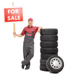 Mechanic standing by a pile of tires and holding for sale sign Royalty Free Stock Photo