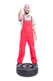 Mechanic standing on top of car wheel and showing like Royalty Free Stock Photo