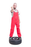 Mechanic standing on top of car wheel showing middle finger Stock Photos