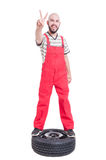 Mechanic standing on top of car wheel and showing victory Stock Photography