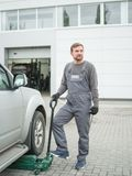 The mechanic stands near the car and holds a jack-screw outdoors. Royalty Free Stock Image
