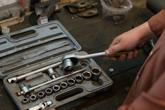Mechanic take tool from the big set tools, wich lying on the des Royalty Free Stock Images