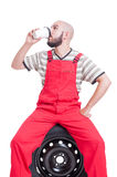 Mechanic taking a break and drinking coffee Stock Images