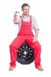 Mechanic taking a break and drinking coffee to go. Sitting on w car wheel Royalty Free Stock Photography