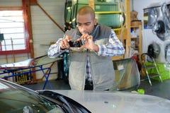 Mechanic taking photograph car. Mechanic taking photograph of car Stock Photos