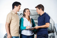 Mechanic Taking Sign From Couple Royalty Free Stock Photography