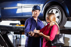 Mechanic Taking Sign On Document From Customer Royalty Free Stock Images