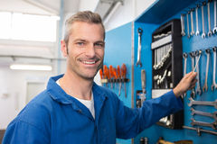 Mechanic taking a tool from wall Royalty Free Stock Images
