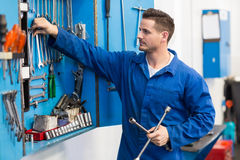 Mechanic taking a tool from wall Stock Photo