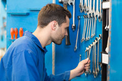 Mechanic taking a tool from wall Stock Images