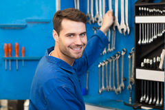 Mechanic taking a tool from wall Royalty Free Stock Photos