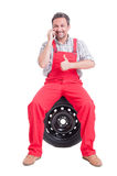 Mechanic talking on phone and showing like Royalty Free Stock Image