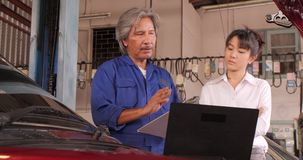 Mechanic talking to a female customer in the garage. stock footage