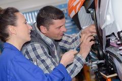 Mechanic teaching intern best practice. Mechanic teaching an intern the best practice Royalty Free Stock Photos