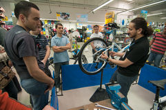 Mechanic teaching people how to adjust the rear derailleur. At a bicycle repair workshop in Decathlon store Stock Photo