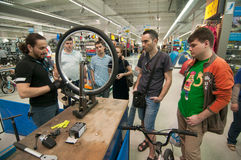 Mechanic teaching people how to true a bike wheel on a truing stand Stock Photo