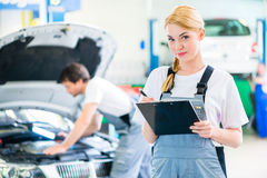 Mechanic team working in car workshop Royalty Free Stock Photo