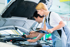 Mechanic team working in car workshop Stock Photos