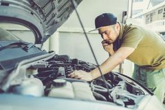 Mechanic, technician man holding clipboard and check the car eng royalty free stock photo
