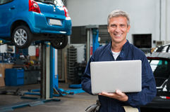 Mechanic Technology. Portrait Of Happy Mature Mechanic At Repair Service Station With Laptop royalty free stock photos