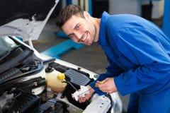 Mechanic testing oil in car Royalty Free Stock Photos