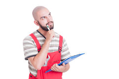 Mechanic thinking holding a clipboard and pen Stock Images