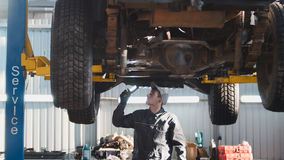 Mechanic with thr lamp is checking the bottom of SUV car in garage automobile service, wide angle Royalty Free Stock Photo