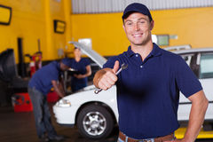 Mechanic thumb up. Happy male auto mechanic giving thumb up holding wrench Royalty Free Stock Photos