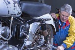 Mechanic tightening a motorbike absorber Stock Photos