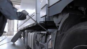 A mechanic tilt down the truck cabin at a truck service station.