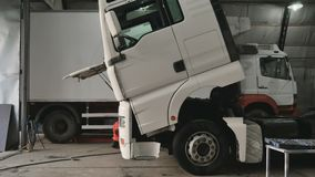 Mechanic tilting cabin of truck. Auto mechanic sits on crouches near the truck in car service station. The man raise the cabin of truck. Tilting the cabin of stock video footage
