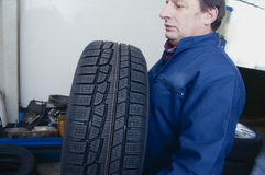 Mechanic and tire Royalty Free Stock Photo