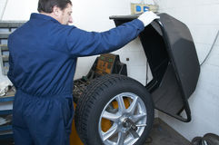 Mechanic and tire Stock Image