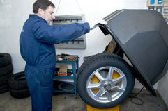 Mechanic and tire. Mechanic repairs a tire in a garage stock image
