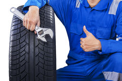 Mechanic with a tire showing thumb up Royalty Free Stock Photography