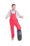 Mechanic with tire showing thumbs up or like gesture. Isolated on white Royalty Free Stock Photo