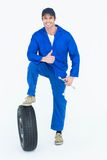 Mechanic with tire and wheel wrenches gesturing thumbs up. Portrait of handsome mechanic with tire and wheel wrenches gesturing thumbs up over white background Royalty Free Stock Images