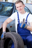 Mechanic with a tire Royalty Free Stock Image