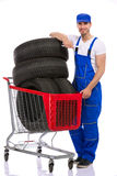 Mechanic with  tires in shopping cart Stock Photography