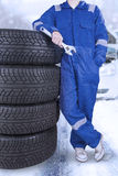 Mechanic and tires in the snow road. Young mechanic wearing blue uniform and holding a wrench while standing near a pile of tires in the snow road Royalty Free Stock Images