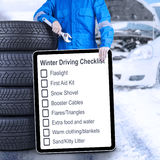 Mechanic with tires and winter driving tips Royalty Free Stock Image