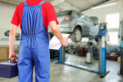 Mechanic with a tool box and clipboard standing in a repair. Mechanic with a tool box and clipboard standing in a car repair service stock photography