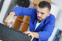 Mechanic with tool changing tyre car. Mechanic with tool changing tyre of car royalty free stock photo