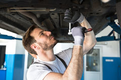 Mechanic with a tool under the car. Mechanic with a tool repair under the car in a workshop royalty free stock photography
