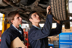 Mechanic And Trainee Working On Car Together Royalty Free Stock Photo