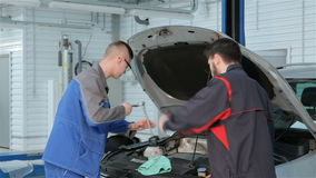 Mechanic troubleshoots car problem at the car service. Young mechanic dressed in blue uniform troubleshooting car problems at the car service. Blond guy in stock video footage