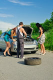 Mechanic and two girls. Near the broken car on a road stock images
