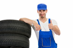 Mechanic with tyre giving a thumbs up Royalty Free Stock Photography
